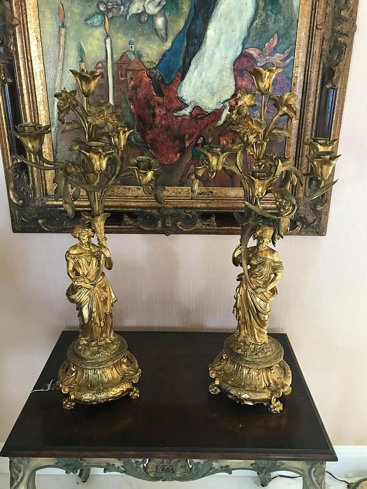 """Pair of 19th Century Gilt Bronze Six-Light Candelabras - Base is raised on clawed feet, centered by a classical maiden holding a floral form stem. Condition: Good, with minor normal wear, one candelabra has a bobeche missing. Dimensions: 30"""" H."""
