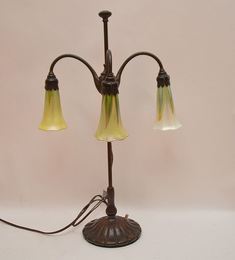 Tiffany Studios New York Bronze student lamp with 3 lily form shades, 21