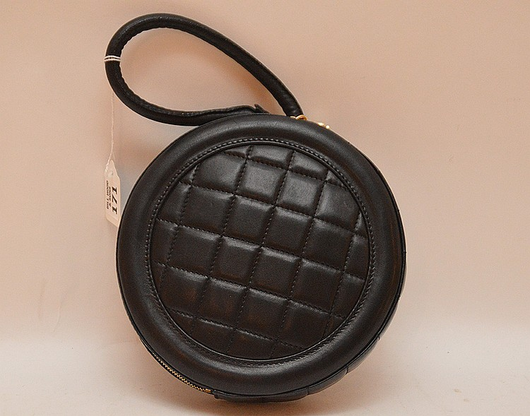 Coco Chanel black leather handbag, round with logo on one side and quilting on other, wristlet handle, Numbered # 7941011, with authentication card inside, felt bag