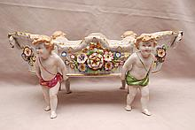 German porcelain centerpiece on figural supports, 16 1/2