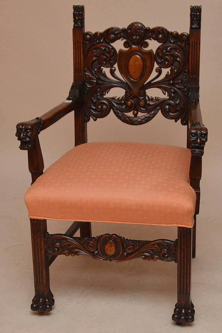 Heavily carved Spanish style arm chair, peach color upholstery