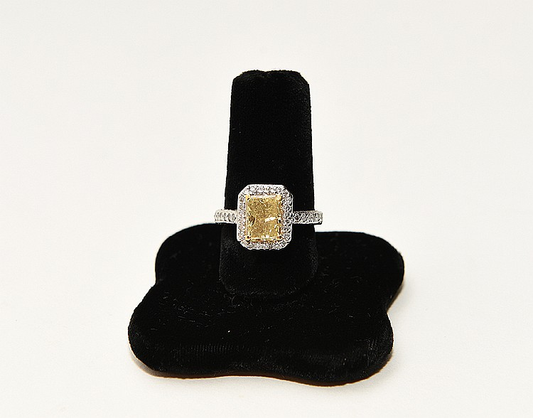 Ladies platinum ring containing a princess cut natural fancy yellow diamond center stone, Clarity SI 3, Carat weight 2.22, surround by round brilliant cut diamonds, Clarity SI 1 - SI 2, Color H, total Carat weight .95