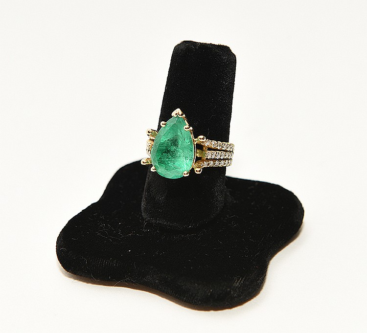 Ladies 18kt yellow gold ring containing a pear shaped emerald center stone measuring 15.15 x 10.17 x 7.04mm, Clarity SI, color medium light very slightly bluish green, estimated Carat weight 5.68ct with round brilliant cut diamonds, Clarity VS 1 - SI