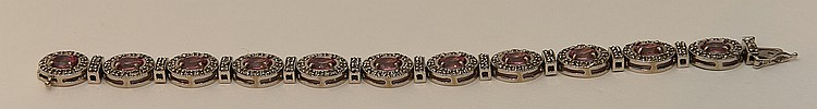 Ladies 14kt white gold bracelet with eleven oval 10.15ctw pink topaz stones and 3.06ctw diamonds