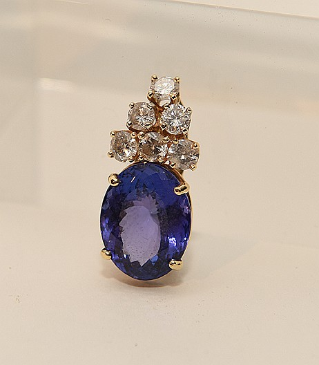 Ladies custom made 14kt yellow gold pendant containing an oval cut tanzanite measuring 16.37 x 12.83 x 8.37mm, Clarity VS, color dark violet, carat weight 12.22 ct and six round brilliant cut diamonds, clarity SI 2 - I 1, Color I/J, total carat