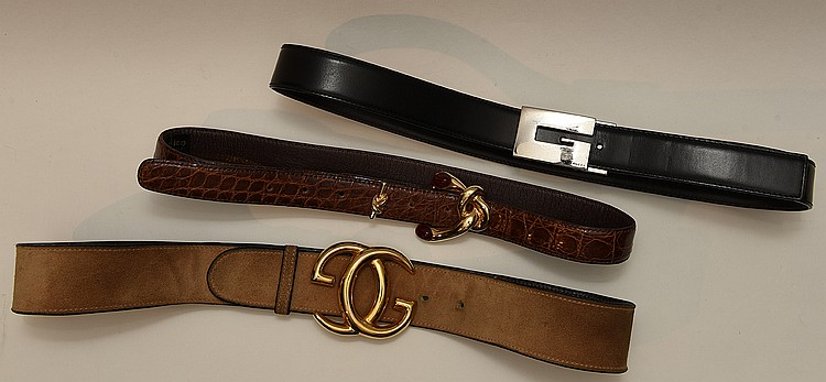 "Set of Three Designer Belts. a) Gucci brown suede with a large gold tone metal double ""G"" buckle (3 ½""x21/2"") . Stamped on belt Gucci made in Italy & incised on buckle, 32""l. b) Black Gucci belt with silver metal ""G"" buckle 2 ½ x 1"