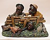 Antique Black Americana Painted Plaster Figural Group.  Depicting Three figures looking over and under a fence.  With indistinct copyright stamp on the back circa 1900.  Ht. 12