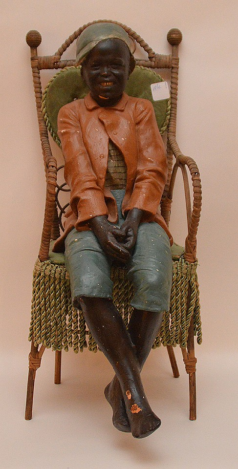 Early 20th Century Black Americana Seated  Painted Plaster Figure.  On a Miniature Victorian Style Wicker Chair.  Ht. 21