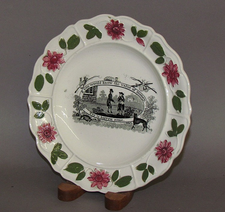 Creamware motto plate with raised floral decoration on border