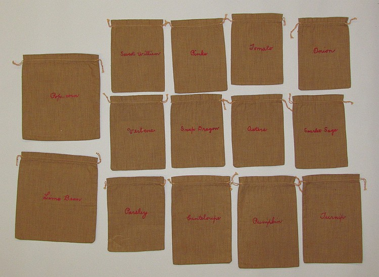 Group of 14 rare seed bags with embroidered names of seeds