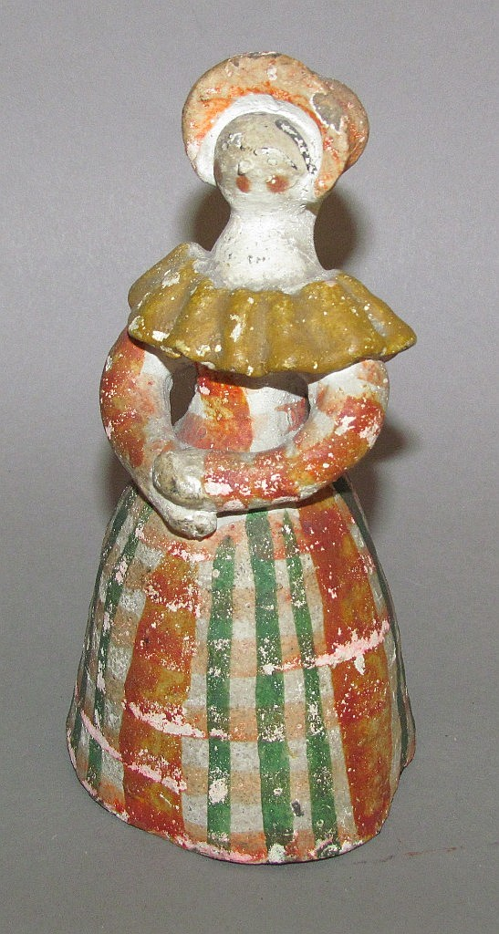Chalkware figure of a young woman with a bonnet and a striped petticoat
