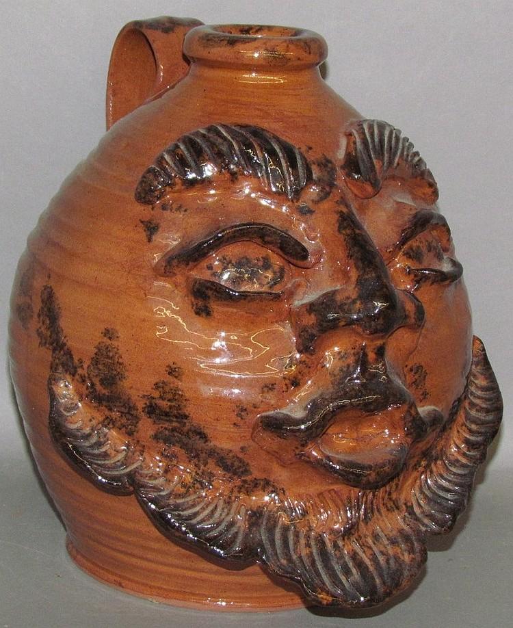 Lot 29: Handled redware face jug
