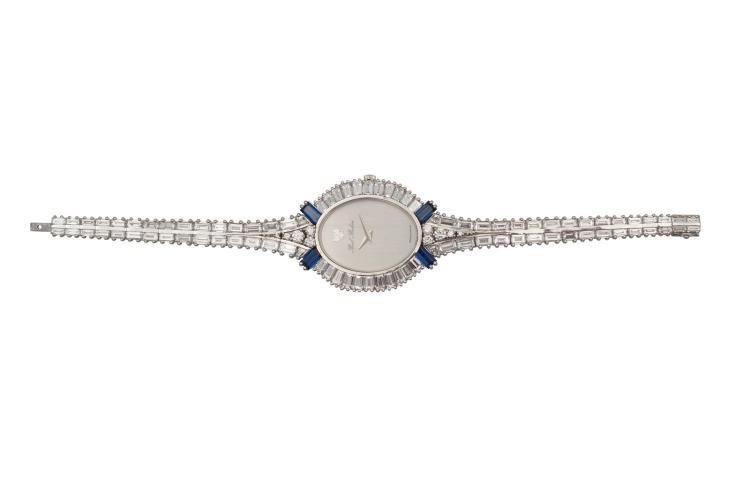 Montre en or gris 750 signée Paul BUHRE, sertie de 88 diamants baguette représentant environ 20 carats et de 8 diamants représentant 0.40 carat, et 4 baguettes saphirs Poids total 44,8 gr Longueur totale 16 cm Avec attestation pour valeur d'assurance de CHF 95000.- A bright 18k white gold lady's watch set with diamonds