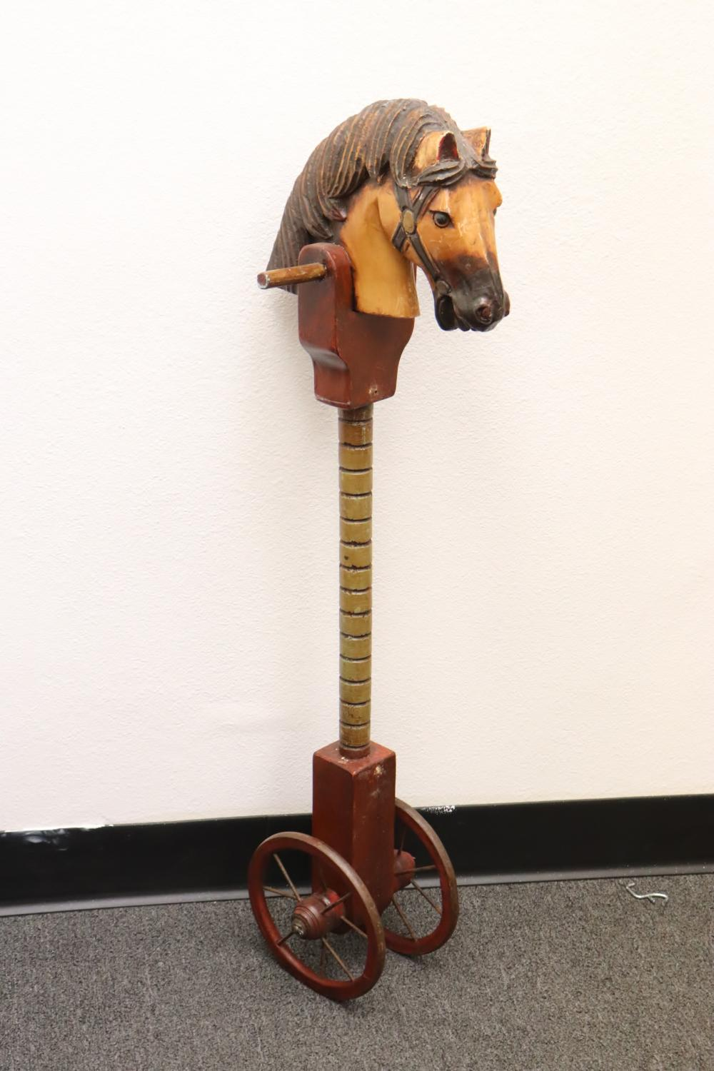 Wood carved hobby horse on wheel