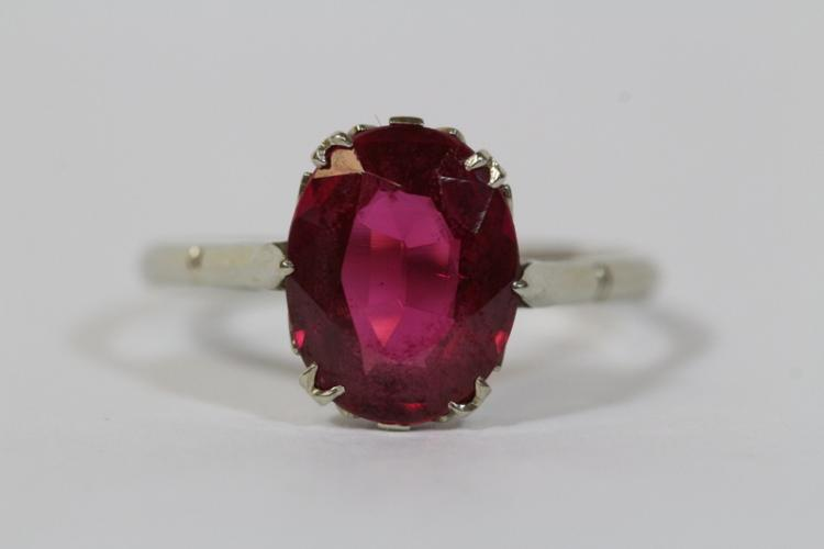 A platinum ring, center a red stone