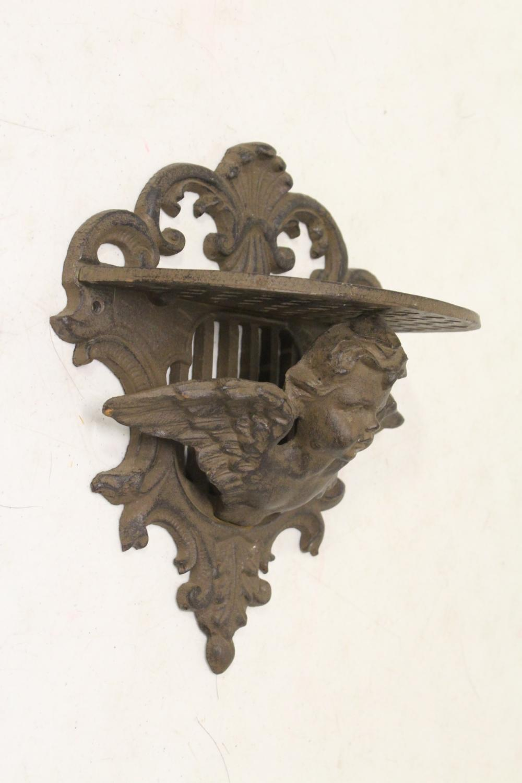 Lot 106: Cast iron wall shelf, and an angel motif ornament