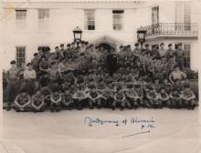 MONTGOMERY B. L.: (1887-1976) British Field Marshal of World War II. Signed 8.5 x 6.5 photograph of Montgomery standing in a full length pose, in uniform, at the centre of a large group of young military officers, standing and seated together in rows, all in uniform, before a large white building. Signed ('Montgomery of Alamein F.M.') in bold blue fountain pen ink with his name alone to a clear area at the base of the image. Some light overall surface and corner creasing, G
