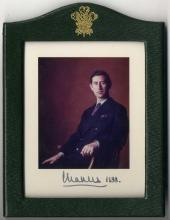 CHARLES: (1948-  ) Prince of Wales. Signed colour 5½ x 7 photograph, the image depicting the Prince seated in a half-length pose. Signed ('Charles') in bold dark fountain pen ink to the lower photographer mount and dated 1988 in his hand. Framed and glazed in the original dark green leather frame by Andrew Soos with gold embossed Prince of Wales feathers at the head. About EX