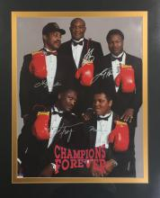 BOXING: Signed colour 15 x 19½ photograph by the World Heavyweight Champion boxers Muhammad Ali, Joe Frazier, Larry Holmes, George Foreman and Ken Norton individually, the image depicting the five boxers standing and seated in full length poses together. All five have signed in silver ink with their names alone to the image. Matted in black and gold. Framed and glazed in a gold coloured frame to an overall size of 26½ x 30½. Together with a companion video cassette titled Champions Forever, featuring the momentous fights that Ali, Frazier, Holmes, Foreman and Norton competed in. About EX, 2