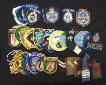 Blue biscuit tin with 57 world police patches, badges and buttons.