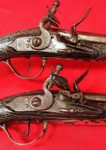A pair of 24 bore Turkish silver coloured metal mounted flintlock holster pistols