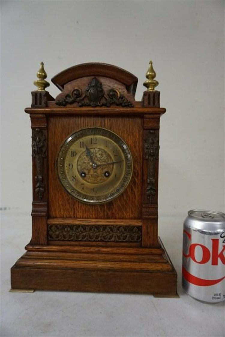 QUALITY OAK MANTEL CLOCK WITH BRASS FINIALS, DECORATIVE FACE, RUNNING, HAS NO. 3207 ON WORKS, HAS PENDULUM, NO KEY, DECORATIVE BRASSS TRIM ON FRONT, MEASURES 14