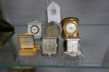 6 MINIATURE NOVELTY CLOCKS & WATCHES, INCLUDING 2 PURSE WATCHES, 1 TRAVEL WATCH, 1 HAS A MUSIC BOX & 2 VERY SMALL CLOCKS, FROM THE MARS COLLECTION, AS PICTURED