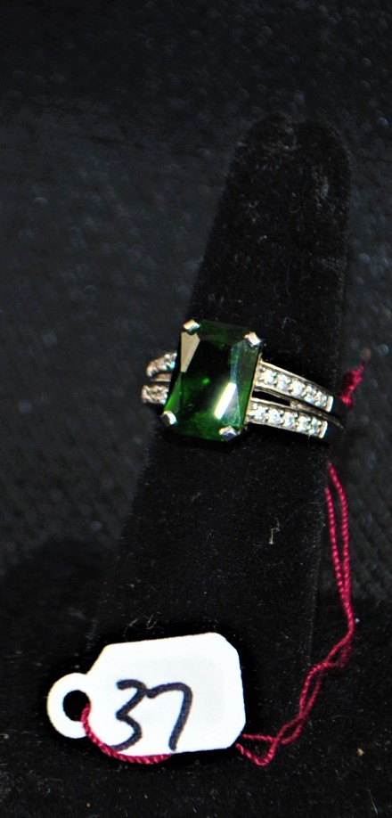 LADIES 14K (STAMPED) WHITE GOLD DIAMOND AND CHROME DIOPSIDE RING. THE RING IS PRONG SET WITH (20) 1.1-1.3MM ROUND FULL CUT DIAMONDS FOR A TOTAL CARAT WEIGHT OF .15CTTW. ALL ROUND FULL CUT DIAMONDS HAVE A MINIMUM COLOR GRADE OF I AND CLARITY GRADE OF I1. THE CENTER OF THE RING IS PRONG SET WITH 11.58 X 8.27MM EMERALD SHAPE CHROME DIOPSIDE WEIGHING APPROX. 4.00CT. THE CHROME DIOSIDE IS DOUBLE AA QUALITY. ALL GEMSTONES WERE GRADED WHILE SET IN THE MOUNTING AND CARAT WEIGHTS WERE CALCULATED BY FORMULA. THE TOTAL METAL WEIGHT WITH GEMSTONES: 5.5 GRAMS. THE TOTAL RETAIL REPLACEMENT VALUE: $2,200.00. AND COMES WITH THE APPRAISAL FOR INSURANCE PURPOSES.