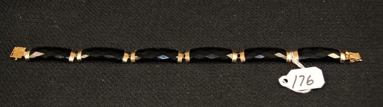 LADIES 14K (STAMPED) YELLOW GOLD ONYX BRACELET. THE BRACELET HAS (6) 8.9X27 OMM ONYX LINKS FOR A TOTAL LENGTH OF 7 INCHES. THE BRACELET IS EQUIPPED WITH A TONGUE STYLE CLASP TOTAL WEIGHT WITH GEMSTONES: 11.2 GRAMS. THE TOTAL REPLACEMENT VALUE: $600.00. AND COMES WITH THE APPRAISAL FOR INSURANCE PURPOSES.