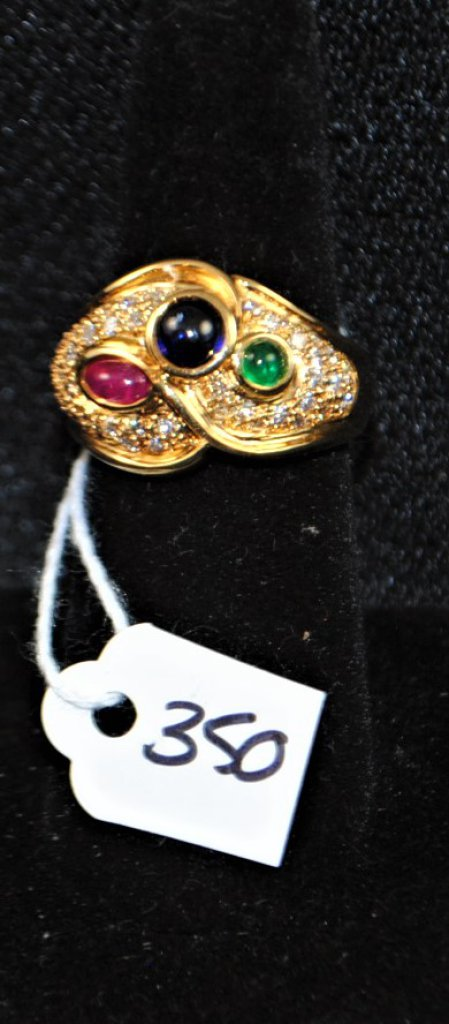 LADY'S 18K YELLOW GOLD FASHION RING CONSISTING OF ONE ROUND GENUINE CABOCHON CUT BLUE SAPPHIRE MEASURING APPROX. 4.5MM, ONE ROUND CABOCHON CUT GREEN EMERALD MEASURING APPROX. 2.9MM, AND ONE OVAL SHAPED CABOCHON CUT GENUINE RED RUBY MEASURING APPROX. 5.6X3.0MM. THE STONES ARE ACCENTED BY 41 ROUND FULL CUT DIAMONDS MEASURING APPROX. 1.0-1.2MM AND WEIGHING 1/2CTTW, GRADE H/SI1. THE DIAMONDS ARE PAVE SET INTO THE RING MEASURES 15MM AT THE TOP AND 5.0MM AT THE BOTTOM OF THE SHANK. SIZE 6 1/2, WEIGHS 6.6DWT. REPLACEMENT VALUE: $4,500.00. AND COMES WITH THE APPRAISAL FOR INSURANCE PURPOSES