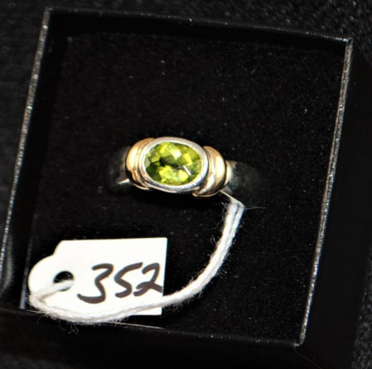 LADY'S STERLING SILVER AND 18K YELLOW GOLD FASHION RING CONSISTING OF ONE GENUINE OVAL SHAPED PERIDOT MEASURING APPROX. 8X6MM AND SET INTO THE STERLING AND ACCENTED WITH THE 18K YELLOW GOLD. SIZE 7, WEIGHS 4.5 DWT. REPLACEMENT VALUE: $250.00. AND COMES WITH THE APPRAISAL FOR INSURANCE PURPOSES.