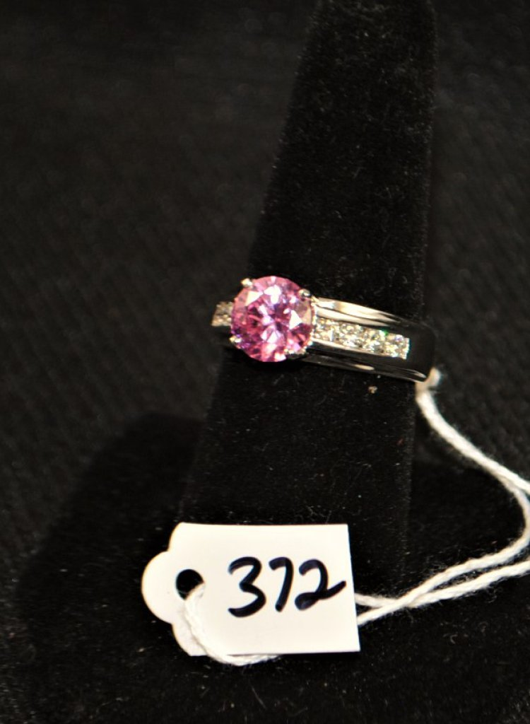 LADY'S 14K WHITE GOLD ENGAGEMENT RING WITH CENTER ROUND 1.5 CARAT SIZE PINK CUBIC ZIRCONIA MEASURING 7.5MM AND 8 ROUND MOISSANITES CHANNEL SET INTO THE 6.5MM BAND. THE MOISSANITES MEASURES APPROX. 2.5MM LIKE A 0.05CT DIAMOND. THE RING TAPERS TO 4.8 MM AT THE BOTTOM OF THE SHANK. RING SIZE 8. WEIGHS 4.2 DWT. REPLACEMENT VALUE: $1,500.00. AND COMES WITH THE APPRAISAL FOR INSURANCE PURPOSES.