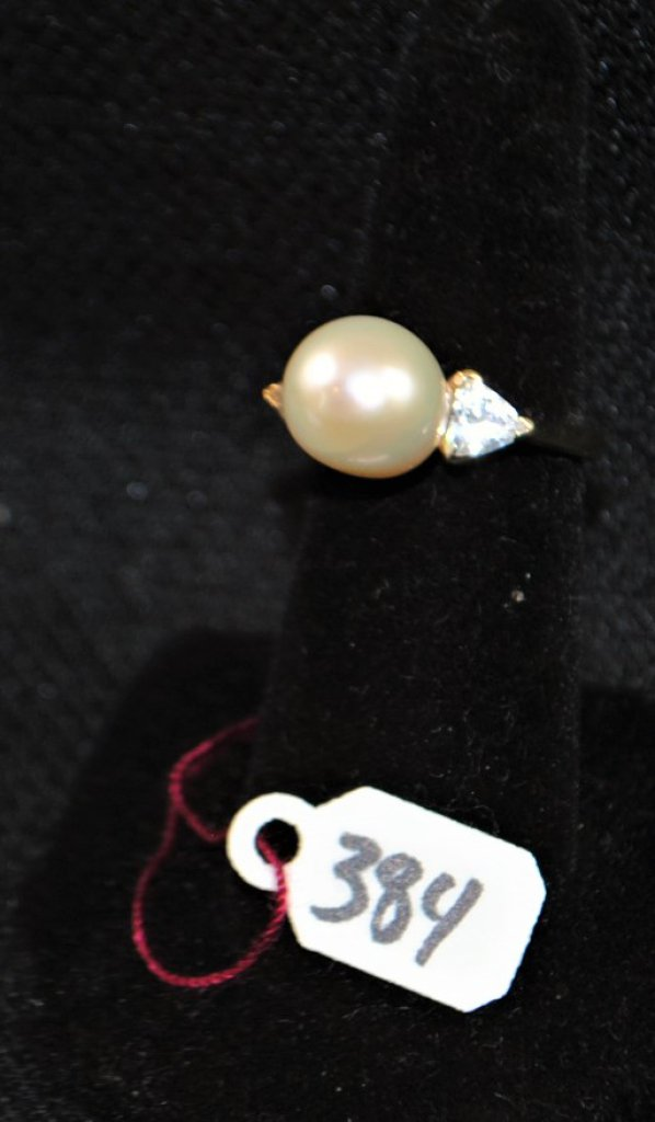 LADYS PEARL RING CONSISTING OF ONE NEAR ROUND, CULTURED PEARL MEASURING APPROX. 10MM WITH TWO PEARL SHAPE CUBIC ZICONS SET INTO 14K YELLOW GOLD MOUNTING, SIZE 6. WEIGHT WITH STONES: 4.0 DWT. REPLACEMENT VALUE: $895.00. AND COMES WITH THE APPRAISAL FOR INSURANCE PURPOSES.