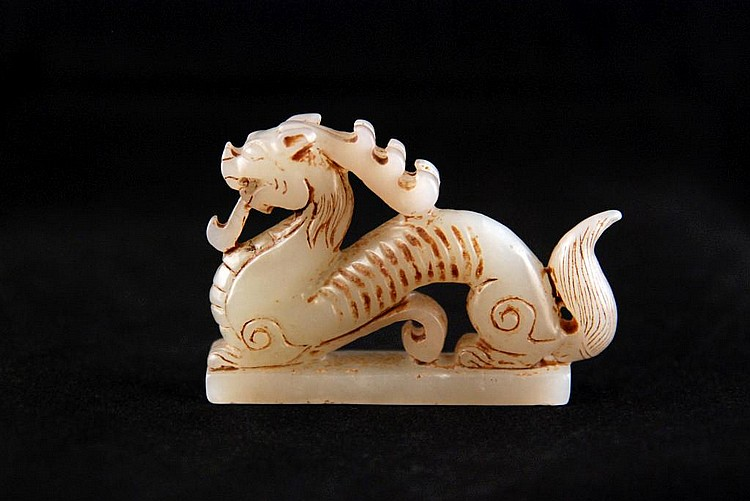 A SMALL WHITE MOTTLED JADEITE DRAGON CARVING
