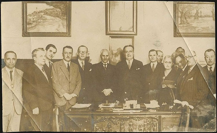 The Minister of Press (1936-1940) Theologos Nikoloudis at his office, with the Foreign Press correspondents. Real photo, sepia, 18 cm x 11 cm. Two serious creases at corners.