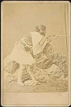 Shooter in greek traditional attire c.1890. Cabinet albumen photo attched to a passe-partout. Reverse: photographers logo. P. Moraites & co, photographer of the royal family.