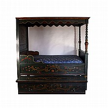 A canopy bed and a chest on the blanket