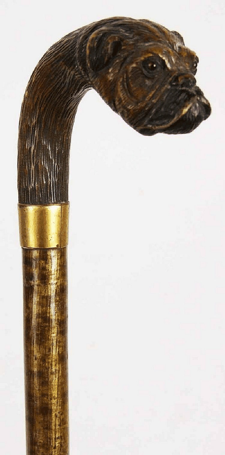 A walking stick, the carved wood handle in the