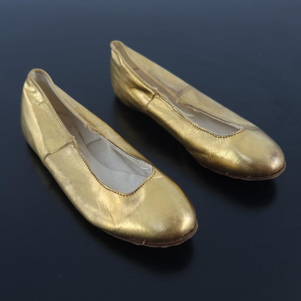 A pair of gold leather shoes for a young