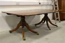 A Regency twin pillar mahogany dining table, including an extendable leaf.
