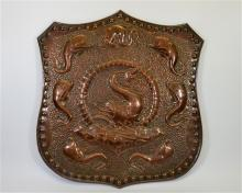 A Newlyn School copper shield shaped plaque, embossed with dolphins, with a