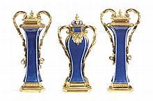 GARNITURE DE CHEMINÉE Chine, dynastie Qing, période Qianlong (1736-1795) pour les porcelaines France, époque Louis XVI, vers 1780 pour les bronzes MATÉRIAUX: Porcelaine et bronzes dorés Vases à bec : H. 36 cm, L. 18 cm, P. 12 cm Vase balustre : H. 35
