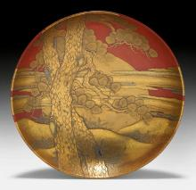 A RED LACQUER DISH DECORATED WITH WINTER THEMES LIKE PINE, PRUNUS AND CRANES IN GOLD AND BLACK.