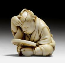 AN IVORY NETSUKE OF A BOY EXAMINING HIMSELF IN A MIRROR.