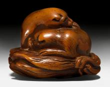A BOXWOOD NETSUKE OF TWO DOGS TIGHTLY NESTLED ON A STRAW RAIN CAPE.