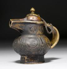 A BRONZE BUTTER-TEA JUG WITH COPPER LID ON A SILVER CHAIN.