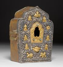 A PARCEL-GILT SILVER G'AU WORKED IN HIGH RELIEF WITH TIBETAN BUDDHIST EMBLEMS.