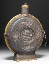 AN IRON MOON FLASK WITH SILVER INLAY AND BRASS MOUNTS.