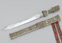 A SHORT SWORD WITH SINGLE-EDGE STEEL BLADE, THE HILT AND SCABBARD OF SKATE SKIN,  POLYCHROME WOVEN RIBBON, AND SILVER WORKED WITH A DESIGN OF RAMPANT BEASTS AMONG FOLIATE SCROLLS.