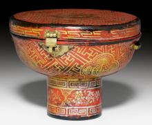 A LACQUERED AND PAINTED WOODEN TRANSPORT CONTAINER FOR A FOOTED CUP SHOWING FLORAL CARTOUCHES AND MEDALLIONS ON A GEOMETRIC PATTERNED GROUND.
